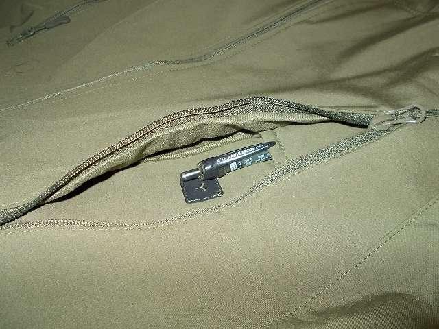 AIKOSHA ソフトシェル タクティカルジャケット M サイズ グリーン(襟タグ ESDY 表記)、D リング付チェストポケットのペンポケットの深さ 約 9cm、三菱鉛筆 油性ボールペン パワータンク SN-200PT-07 クリップがペンポケットに完全に引っ掛けられていない状態(ペンポケットが浅い)