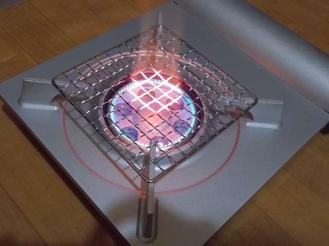 イワタニ カセットフー エコプレミアム CB-ECO-PRW の五徳(ごとく)にパール金属 懐石 卓上コンロ用 焼網 15cm H-6476(鉄・クロムめっき)を置いた状態で着火・点火したところ(火力 大)、ガスの炎が当たる焼き網の網目部分が赤くなる