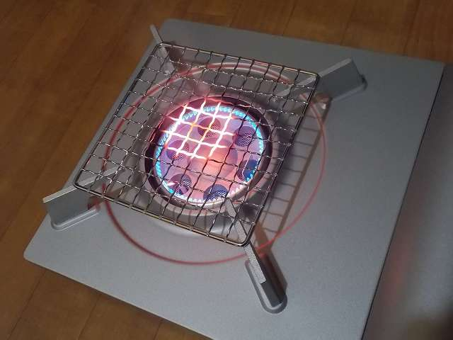 イワタニ カセットフー エコプレミアム CB-ECO-PRW の五徳(ごとく)にパール金属 懐石 卓上コンロ用 焼網 15cm H-6476(鉄・クロムめっき)を置いた状態で着火・点火して火力を下げたところ、ガスの炎が当たる焼き網の網目部分が赤くなる
