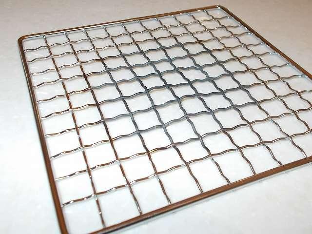 イワタニ カセットフー エコプレミアム CB-ECO-PRW の五徳(ごとく)に置いてガスの炎を当て続けたことで黒色に変色、網目がゆがんだ状態になったパール金属 懐石 卓上コンロ用 焼網 15cm H-6476(鉄・クロムめっき)の裏面側、鉄・クロムめっきでできた焼き網は熱で変形しやすい