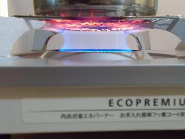 イワタニ カセットフー エコプレミアム CB-ECO-PRW の五徳(ごとく)にパール金属 懐石 卓上コンロ用 焼網 15cm H-6476(鉄・クロムめっき)を置いて、その上に水を入れたステンレス鍋を置いた状態でガスコンロを着火・点火したところ、ガスの炎が鍋底の中心から外側に広がっているのが焼き網の色でわかる
