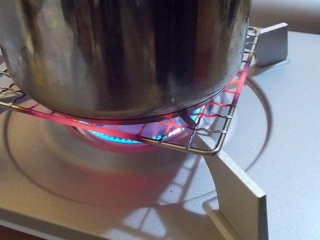 イワタニ カセットフー エコプレミアム CB-ECO-PRW の五徳(ごとく)にパール金属 懐石 卓上コンロ用 焼網 15cm H-6476(鉄・クロムめっき)を置いて、その上にステンレス鍋を置いた状態でガスコンロを着火・点火したところ、ガスの炎が鍋底の中心からさらに外側に広がって、焼き網のフレーム部分にまでガスの炎が届き、フレームが赤くなっている状態