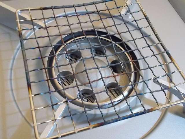 イワタニ カセットフー エコプレミアム CB-ECO-PRW の五徳(ごとく)にパール金属 懐石 卓上コンロ用 焼網 15cm H-6476(鉄・クロムめっき)を置いて、その上にステンレス鍋を置いた状態でガスコンロ使用後の焼網、炎が広範囲に広がったことで焼き網の大部分が黒色に変色、ステンレス鍋+水の重さのせいかフレームも含め大きくゆがんだ焼き網
