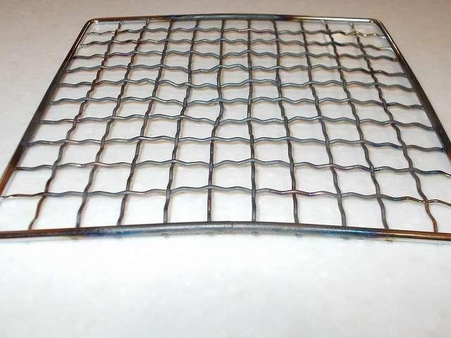 イワタニ カセットフー エコプレミアム CB-ECO-PRW の五徳(ごとく)にパール金属 懐石 卓上コンロ用 焼網 15cm H-6476(鉄・クロムめっき)を置いて、その上にステンレス鍋を置いた状態でガスコンロ使用後の焼網、炎が広範囲に広がったことで焼き網の大部分が黒色に変色、ステンレス鍋+水の重さのせいかフレームも含め大きくゆがんだ焼き網、手で反対側に曲げることで一応まっすぐに戻すことは可能