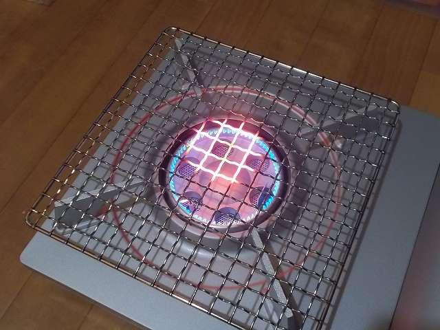 イワタニ カセットフー エコプレミアム CB-ECO-PRW の五徳(ごとく)にユニフレーム ネイチャーストーブ焼き網 SUS210 21cm 角 材質:ステンレス鋼を置いた状態で着火・点火したところ(火力 大)、ガスの炎が当たる焼き網の網目部分が赤くなる