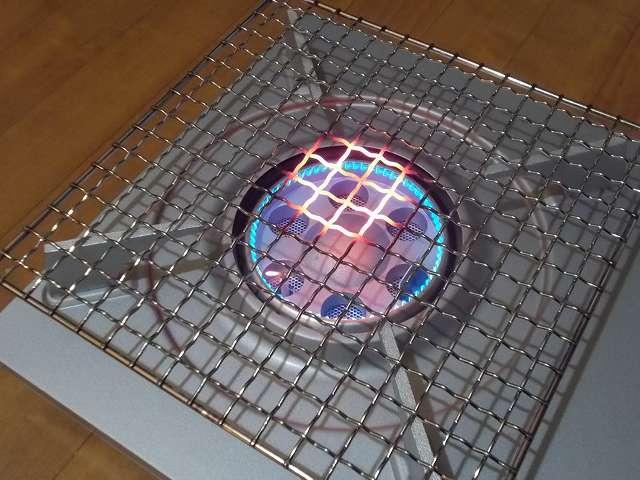 イワタニ カセットフー エコプレミアム CB-ECO-PRW の五徳(ごとく)にユニフレーム ネイチャーストーブ焼き網 SUS210 21cm 角 材質:ステンレス鋼を置いた状態で着火・点火して火力を下げたところ、ガスの炎が当たる焼き網の網目部分が赤くなる