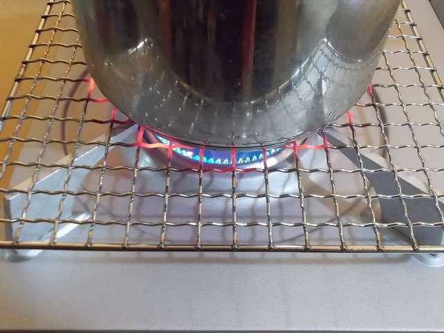 イワタニ カセットフー エコプレミアム CB-ECO-PRW の五徳(ごとく)にユニフレーム ネイチャーストーブ焼き網 SUS210 21cm 角 材質:ステンレス鋼を置いて、その上にステンレス鍋を置いた状態でガスコンロを着火・点火したところ(火力大)