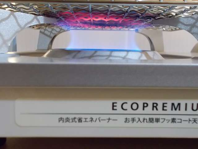 イワタニ カセットフー エコプレミアム CB-ECO-PRW の五徳(ごとく)にユニフレーム ネイチャーストーブ焼き網 SUS210 21cm 角 材質:ステンレス鋼を置いて、その上に水を入れたステンレス鍋を置いた状態でガスコンロを着火・点火したところ、ガスの炎が鍋底の中心から外側に広がっているのが焼き網の色でわかる
