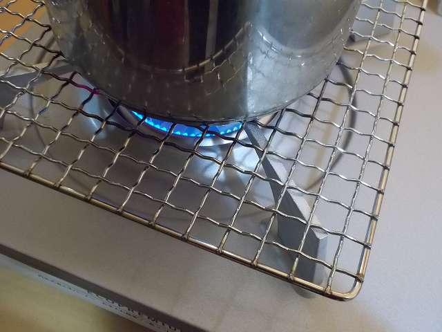 イワタニ カセットフー エコプレミアム CB-ECO-PRW の五徳(ごとく)にユニフレーム ネイチャーストーブ焼き網 SUS210 21cm 角 材質:ステンレス鋼を置いて、その上にステンレス鍋を置いた状態でガスコンロを着火・点火したところ(火力小)