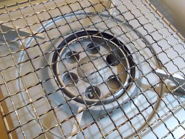 イワタニ カセットフー エコプレミアム CB-ECO-PRW の五徳(ごとく)にユニフレーム ネイチャーストーブ焼き網 SUS210 21cm 角 材質:ステンレス鋼を置いて、その上にステンレス鍋を置いた状態でガスコンロ使用後の焼網、黒く変色している以外は鉄・クロムめっき焼網のような大きなゆがみや変形はなかった