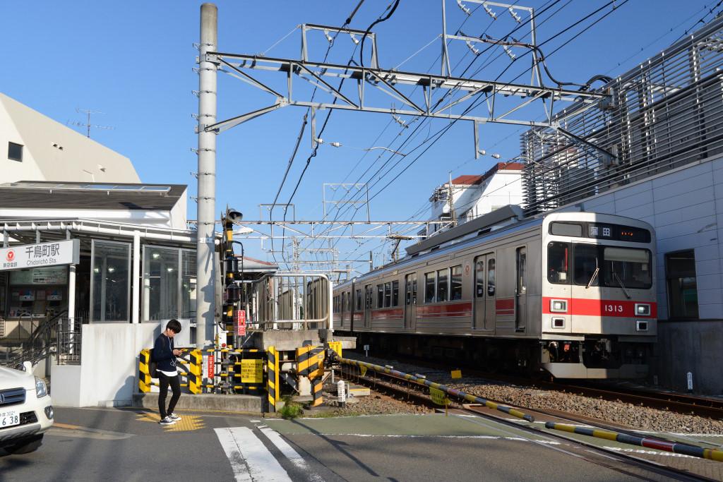 千鳥町駅前踏切を通過する1000系