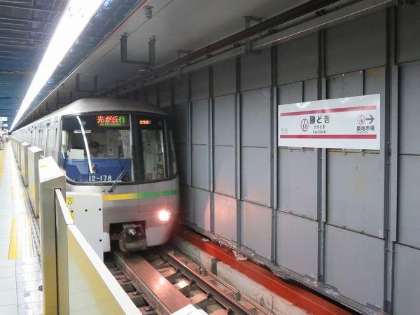 勝どき駅に到着する12-000形電車。壁の裏では新ホームの建設が着々と進んでいる。